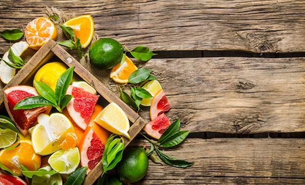 Eine schachtel zitrusfrüchte. grapefruit, orange, mandarine, zitrone, limette und blätter auf holztisch. draufsicht