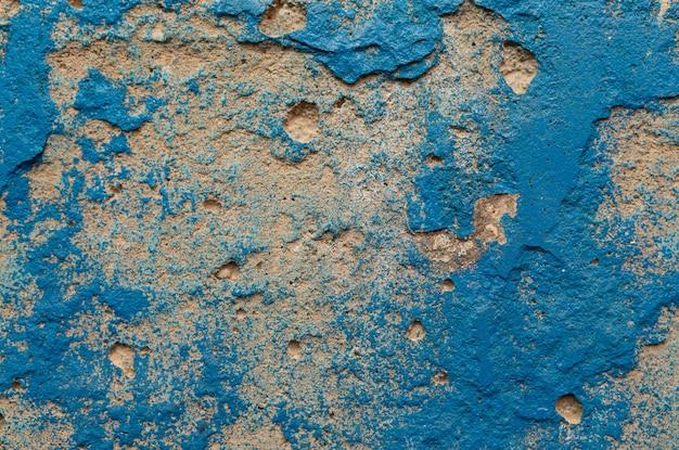 Eine schäbige verputzte wand, die mit satter blauer farbe verschmutzt war