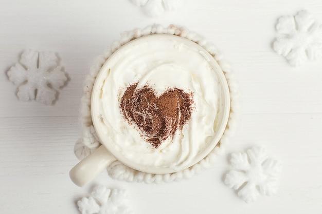 Eine schale des heißen wintergetränks, mit schlagsahne und kakaopulver und weißen schneeflocken auf einem holztisch