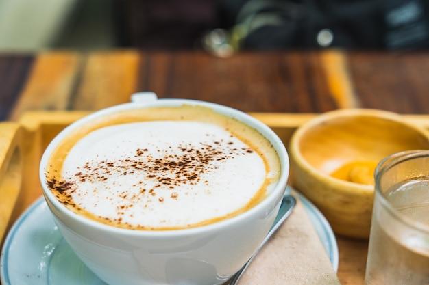 Eine schale heißer cappuccinokaffee auf hölzerner tabelle