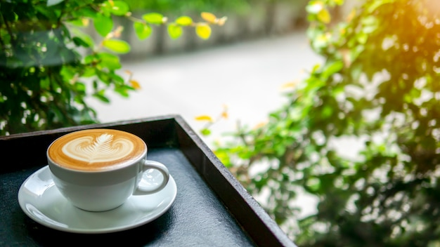Eine schale heißer kaffee mit milchkunst auf holztisch neben fenster sehen durch draußen mit aus