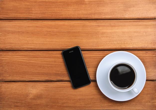 Eine schale heißer kaffee und handy auf einem dunklen hölzernen hintergrund.