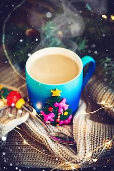 Eine schale heißer kakao in einem weihnachtsbecher auf dem hintergrund von weihnachtsgirlanden