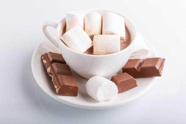 Eine schale heißer kakao mit der eibisch- und milchschokolade lokalisiert auf weiß.