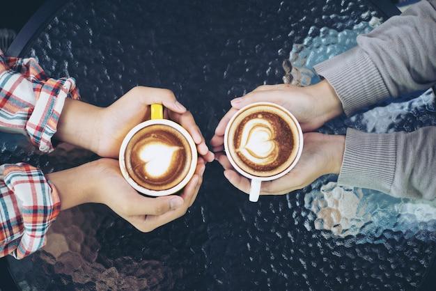 Eine schale lattekunst in der hand. die geliebten sind zusammen weinlesefarbe selektiver fokus