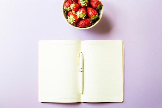 Eine schale mit reifen roten erdbeeren steht neben einem offenen notizblock