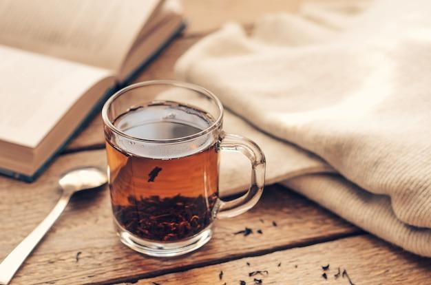 Eine schale mit schwarzem gebrautem tee auf einem holztisch mit buch und einer warmen strickjacke