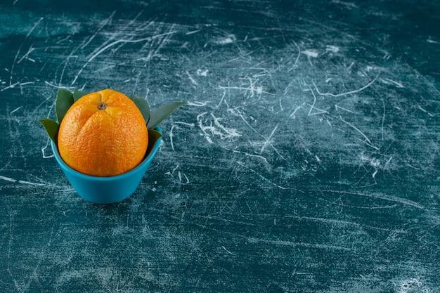 Eine schale orange mit blättern, auf dem marmortisch.