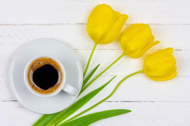 Eine schale schwarzer kaffee auf einer untertasse und einer gelben blume der tulpe drei auf einem weißen hölzernen hintergrund