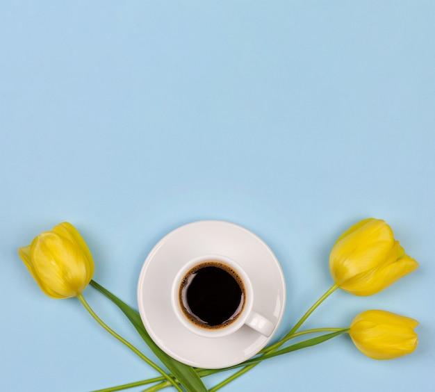 Eine schale schwarzer kaffee auf einer untertasse und einer gelben tulpenblume auf einem blauen hintergrund