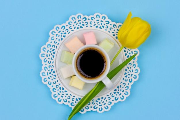 Eine schale schwarzer kaffee, eibisch auf einer untertasse und eine gelbe tulpenblume auf einem blauen hintergrund