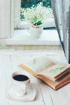 Eine schale schwarzer kaffee und ein offenes buch auf einer retro- tabelle der weißen hölzernen weinlese und ein blumenstrauß des maiglöckchens blüht auf dem fensterbrett am rustikalen morgen des hauses im frühjahr