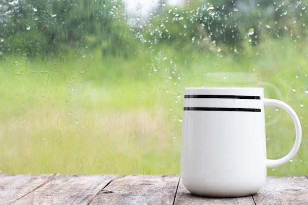 Eine schale setzte an holztabelle neben fenster am regnerischen tag