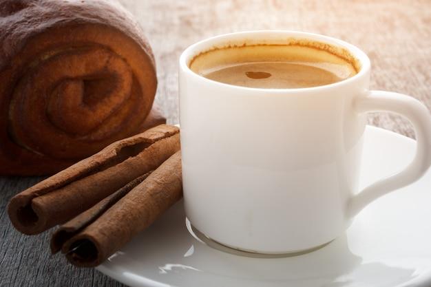Eine schale wohlriechender kaffee auf einer weißen platte auf einem hölzernen hintergrund.