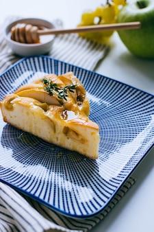 Eine scheibe des frischen apfelkuchens mit trauben und honig auf einer blauen platte. frühstück.