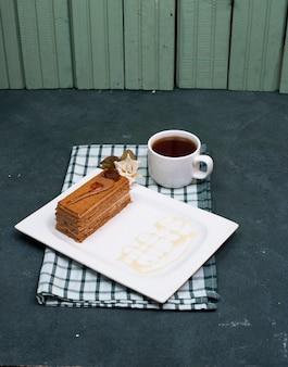 Eine scheibe des schokoladenkakaokuchens in der weißen platte.