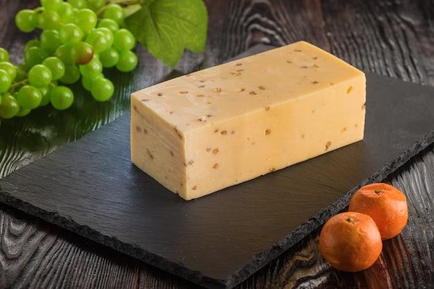 Eine scheibe käse auf einer schiefertafel mit einer traube
