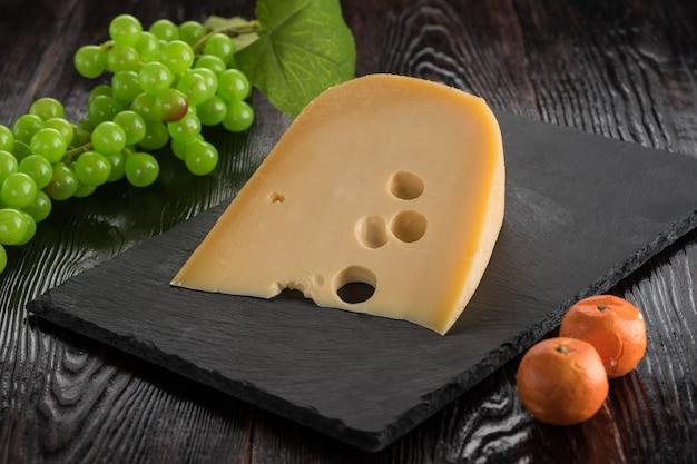 Eine scheibe maasdamer käse auf einem schiefer eber mit einer traube