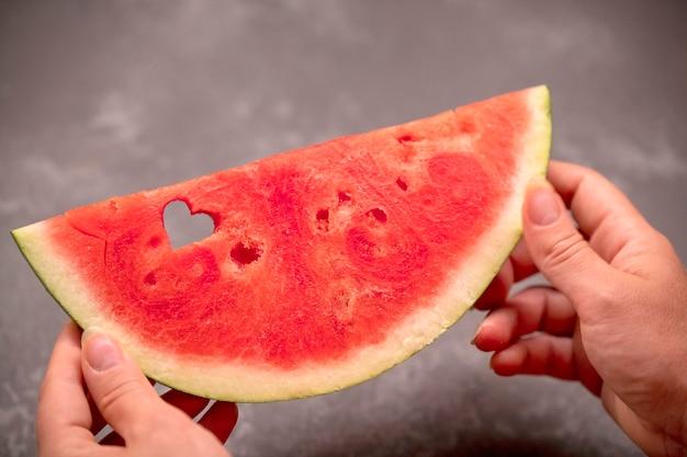 Eine scheibe wassermelone in den händen mit einem herzförmigen loch