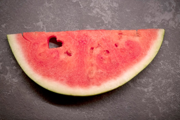 Eine scheibe wassermelone mit einem herzförmigen loch