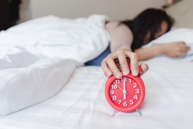 Eine schläfrige asiatische junge frau, die einen wecker hält. bald, um für das schlafen aufzuwachen