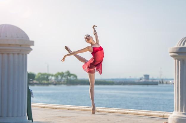Eine schlanke ballerina in spitzenschuhen und einem brautkostüm springt vor dem hintergrund des meeres