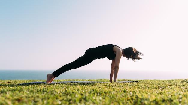 Eine schlanke frau praktiziert yoga im freien. speicherplatz kopieren