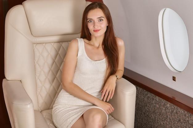 Eine schlanke junge frau in einem privatjet. ein passagier der ersten klasse sitzt auf dem sitz eines firmenfluges.