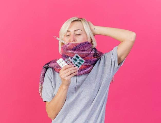 Eine schmerzende junge blonde kranke slawische frau, die einen schal trägt, legt die hand auf den kopf hinter das halten der packungen