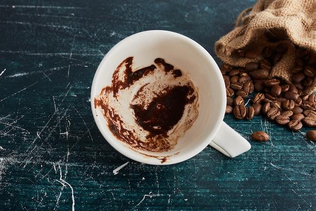 Eine schmutzige tasse kaffee mit bohnen.