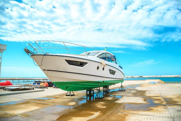 Eine schneeweiße yacht steht auf einem pier auf untersetzern an einem sonnigen tag gegen einen schönen himmel mit wolken
