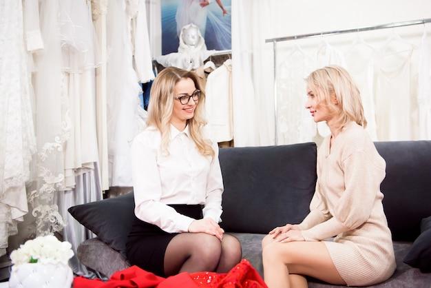 Eine schneiderin spricht mit einem kunden über ein neues kleid.