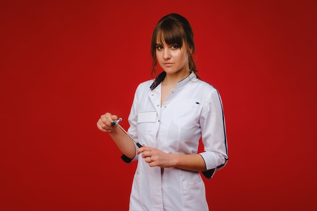 Eine schöne ärztin hält einen reflexhammer und lächelt in die kamera isoliert auf einem roten hintergrund.