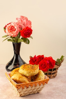 Eine schöne ansicht der roten rosen der vorderansicht rosa und blumen innerhalb des schwarzen kruges zusammen mit qogals innerhalb des brotbehälters lokalisiert auf tisch und rosa