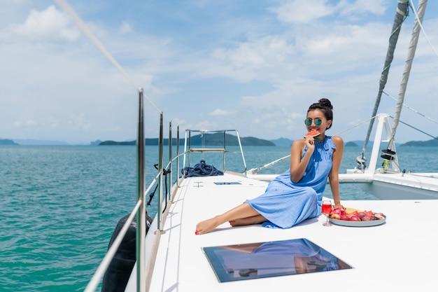 Eine schöne asiatische dame in einem blauen kleid auf einer yacht trinkt champagner und isst früchte
