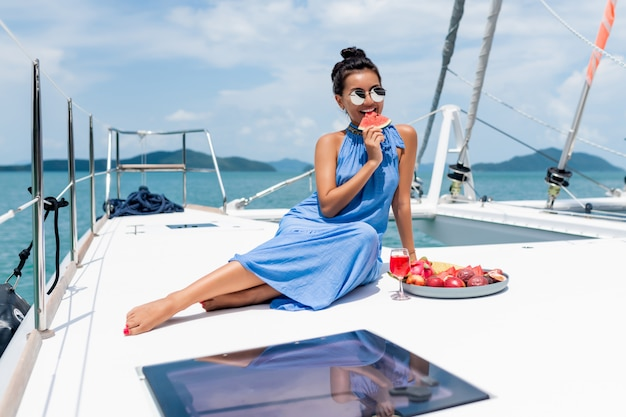 Eine schöne asiatische dame in einem blauen kleid auf einer yacht trinkt champagner und isst obst,