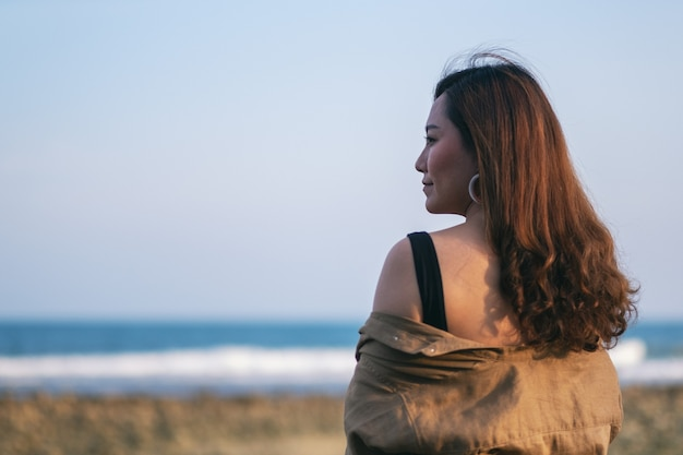 Eine schöne asiatische frau, die am strand an der küste spaziert