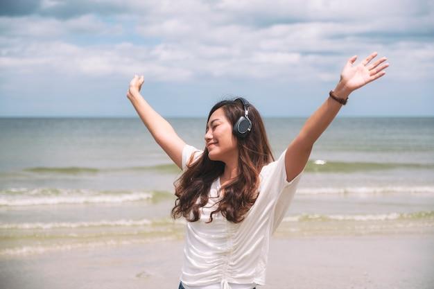 Eine schöne asiatische frau, die arme öffnet, während sie musik mit kopfhörer am meer hört