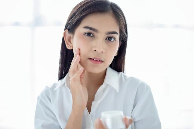 Eine schöne asiatische frau, die ein hautpflegeprodukt, eine feuchtigkeitscreme oder eine lotion verwendet, die sich um ihren trockenen teint kümmert. feuchtigkeitscreme in weiblichen händen.