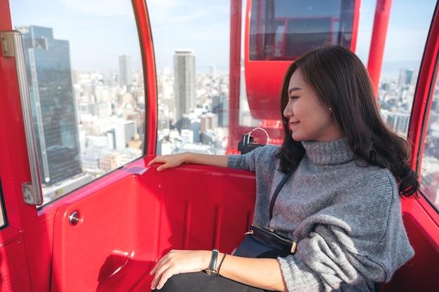 Eine schöne asiatische frau, die ein rotes riesenrad in japan reitet