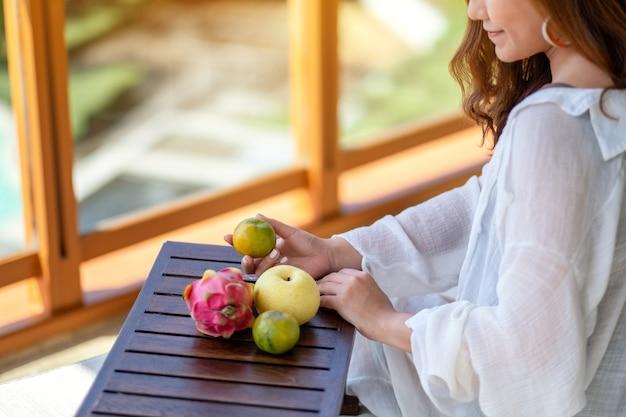Eine schöne asiatische frau, die eine orange mit birnen- und drachenfrucht auf einem kleinen holztisch hält