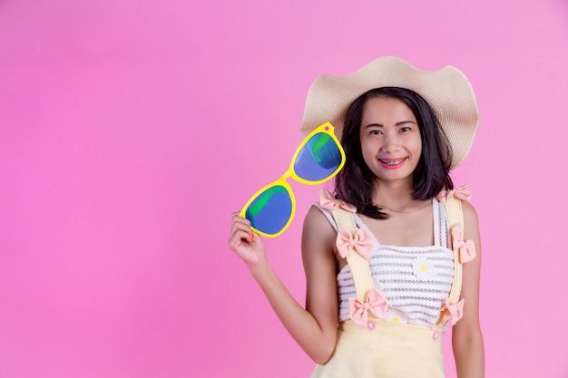 Eine schöne asiatische frau, die einen hut und große gläser mit einem rosa trägt.