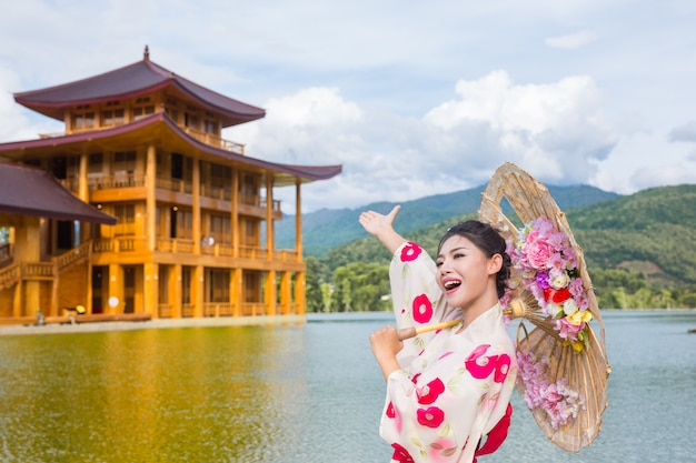 Eine schöne asiatische frau, die einen japanischen kimono, traditionelles kleidkonzept trägt.