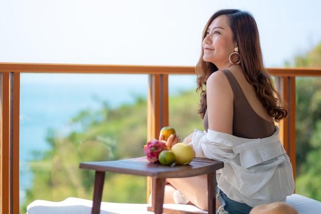 Eine schöne asiatische frau, die früchte hält, während sie am balkon mit dem meerblickhintergrund sitzen genießen