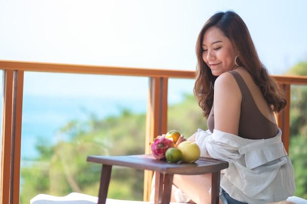 Eine schöne asiatische frau, die früchte hält, während sie auf dem balkon mit meerblickhintergrund sitzt