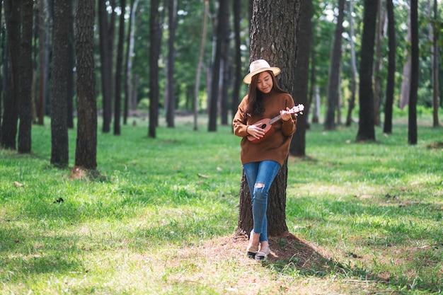 Eine schöne asiatische frau, die im park ukulele steht und spielt