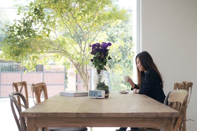 Eine schöne asiatische frau, die kaffee mit dem gefühl entspannt im café hält und trinkt