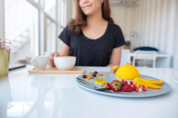 Eine schöne asiatische frau, die kaffee trinkt und orangenkuchen mit gemischten früchten im café isst