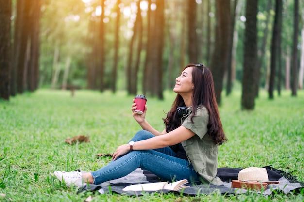 Eine schöne asiatische frau, die kaffee trinkt, während sie im park sitzt