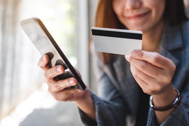 Eine schöne asiatische frau, die kreditkarte für kauf und einkauf online auf handy verwendet